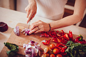 istock Woman cutting onions and vegetables on cutting board 1001438190