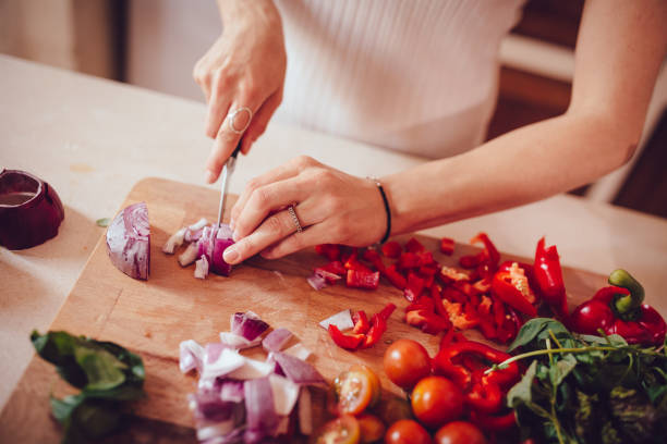 Woman cutting onions and vegetables on cutting board Close-up of woman cutting fresh vegetables while cooking healthy Mediterranean lunch in house kitchen wundervisuals stock pictures, royalty-free photos & images