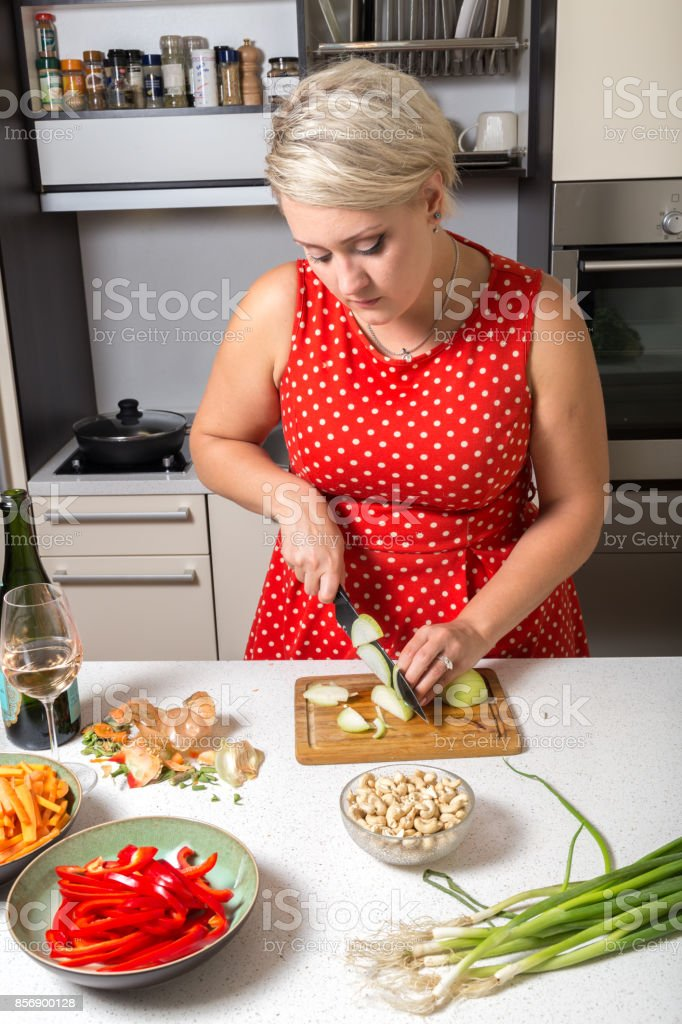 Woman cutting onions in red dotted dress stock photo