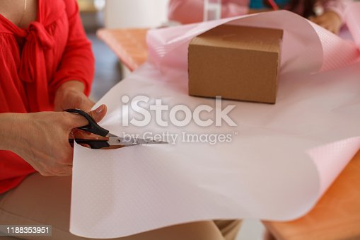 Close-up shot of a woman cutting wrapping paper while preparing presents at home.