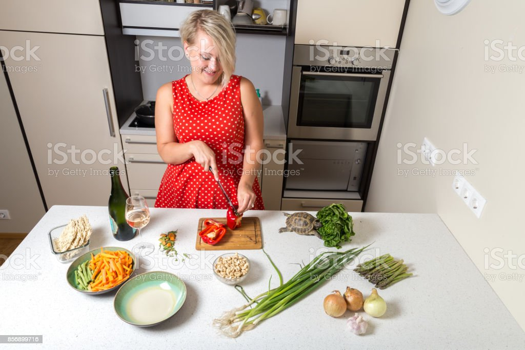 Woman cutting paprika and smiling while turtle eats stock photo