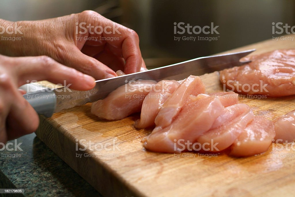 Woman Cutting Raw Chicken on a Wooden Cutting Board stock photo