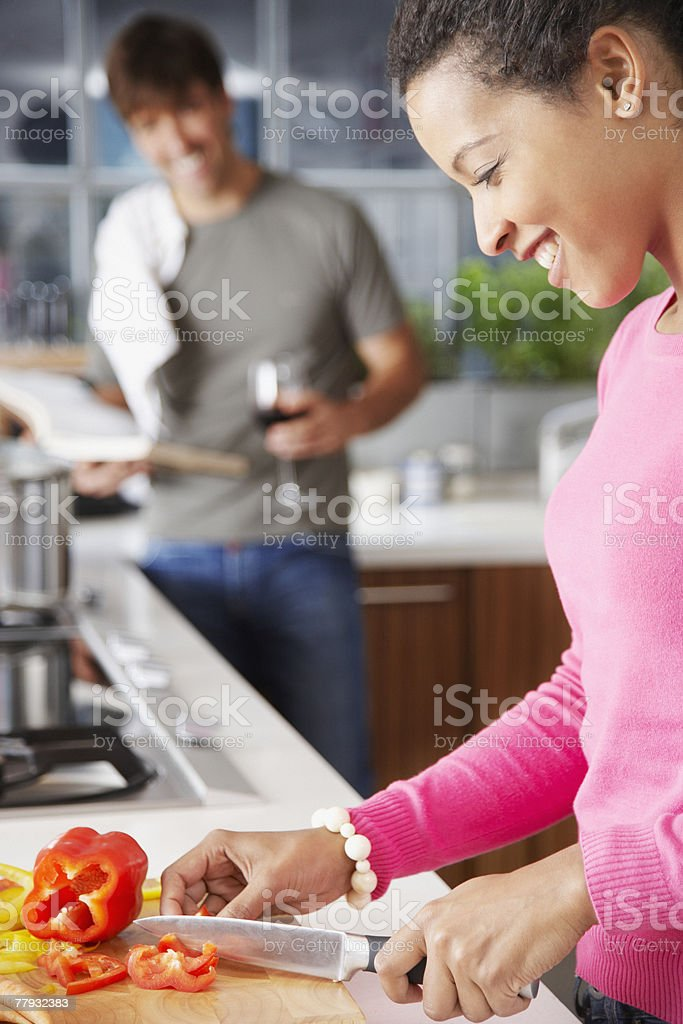 Woman cutting red peppers with man in background stock photo