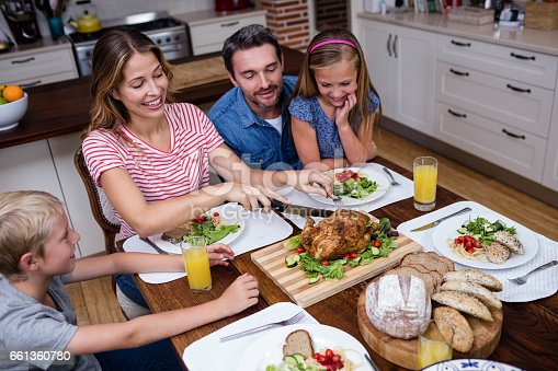 Woman cutting roasted turkey while having meal with his family at home