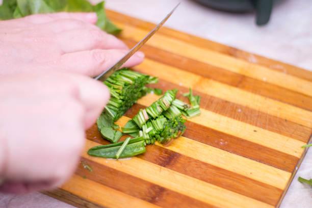 Kadın ahşap pişirme masasında bıçak ile kuzukulağı kesme stok fotoğrafı