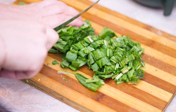 Ahşap yemek masasında bıçakla sorrel kesme kadın stok fotoğrafı