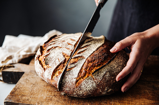 Close-up of woman cutting sourdough bread on board. Midsection of female is with knife and baked bread. She is in kitchen.