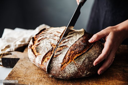 istock Woman cutting sourdough bread with knife on board 1225036973
