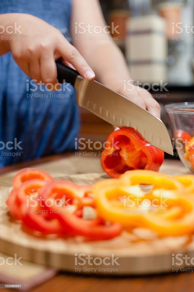 Woman cutting sweet peppers royalty-free stock photo