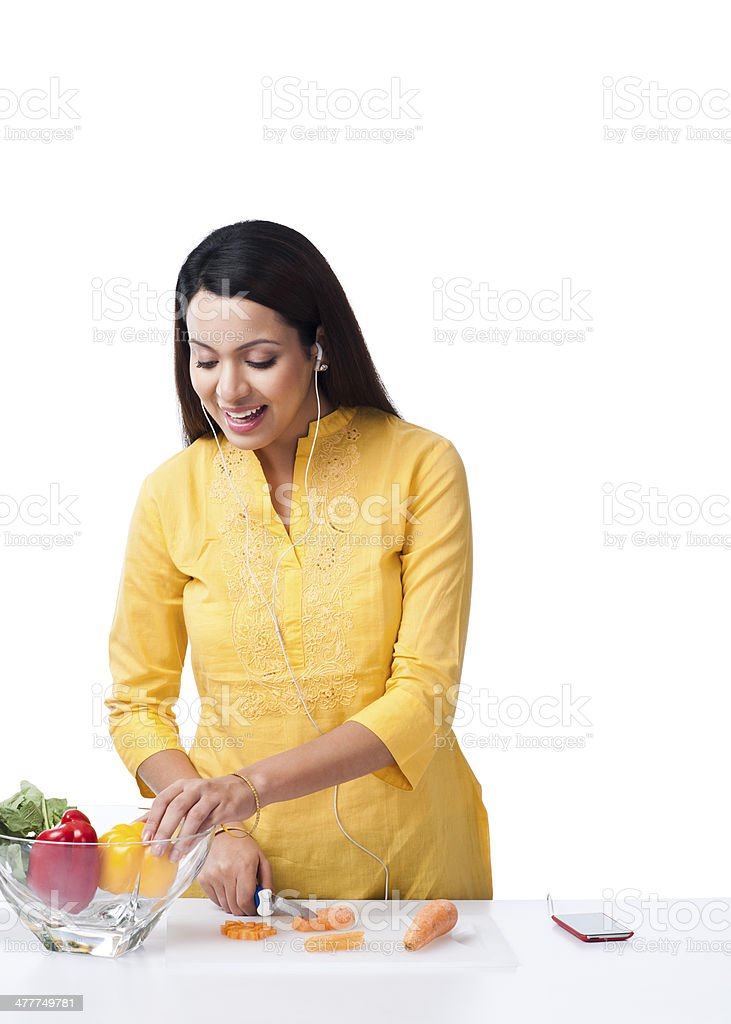 Woman cutting vegetables and listening music with an mp3 player royalty-free stock photo