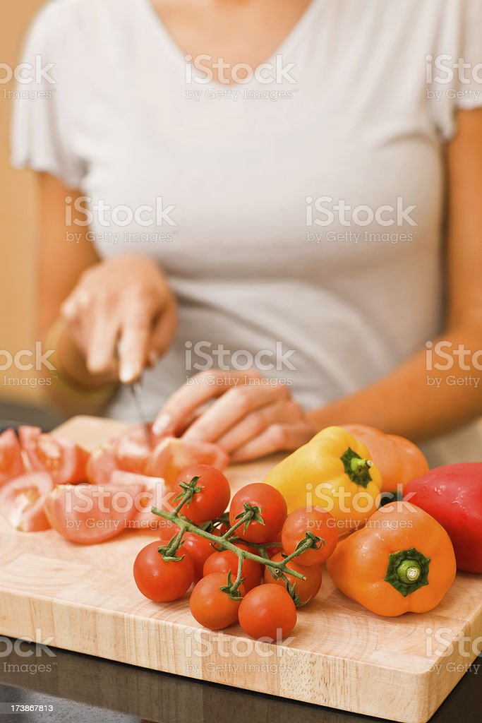 Woman cutting vegetables in kitchen royalty-free stock photo