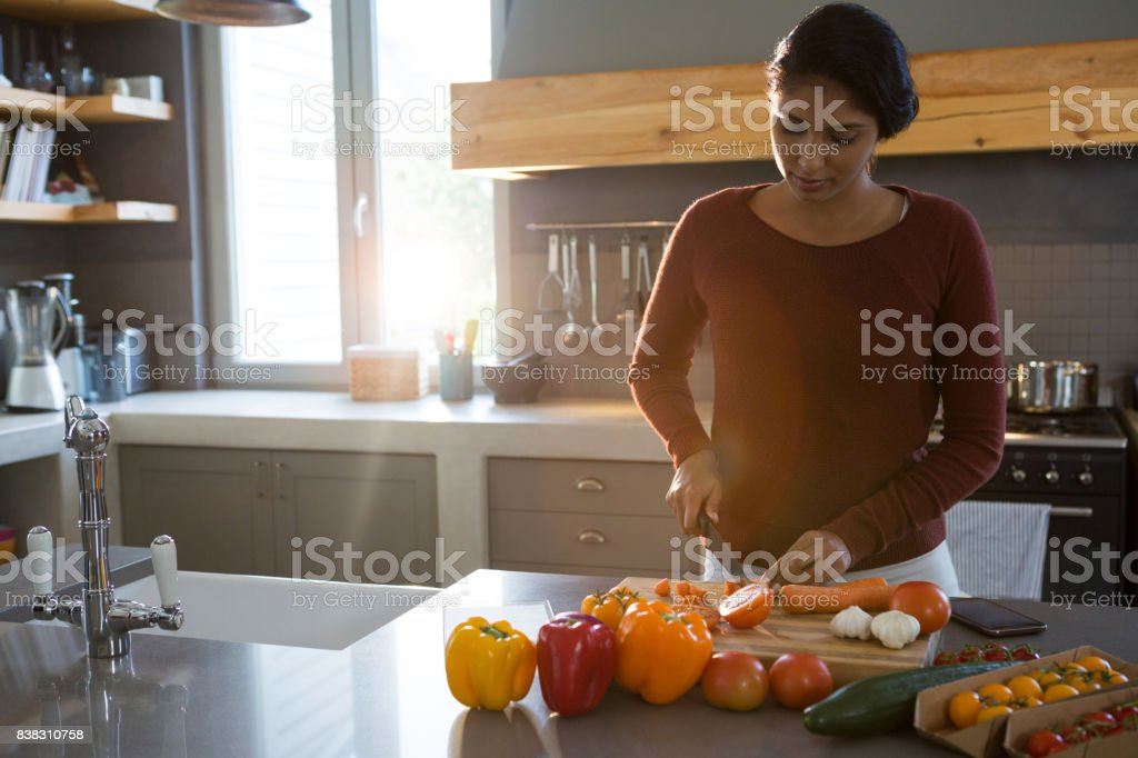 Woman cutting vegetables in kitchen stock photo