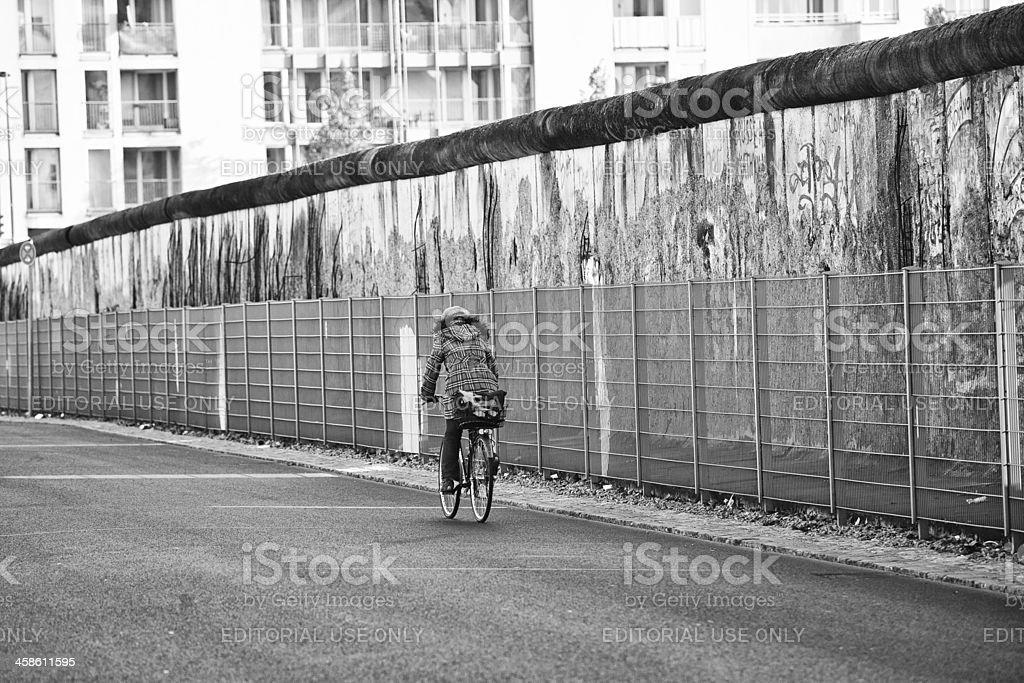 Woman Cycling Along the Ruins of Berlin Wall, Germany stock photo