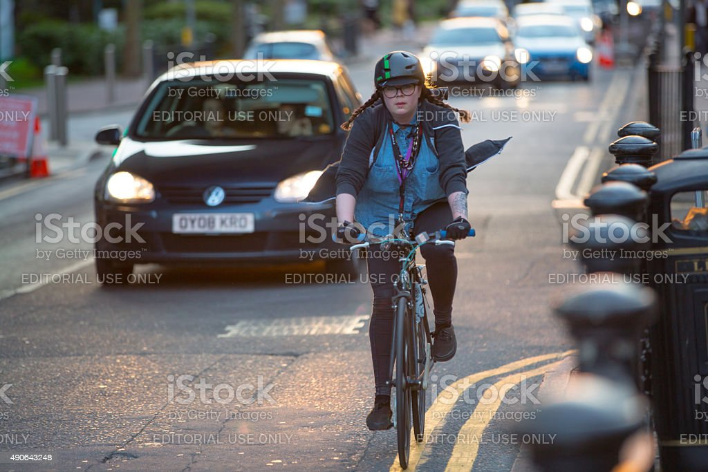 Woman cycling from the work, London stock photo