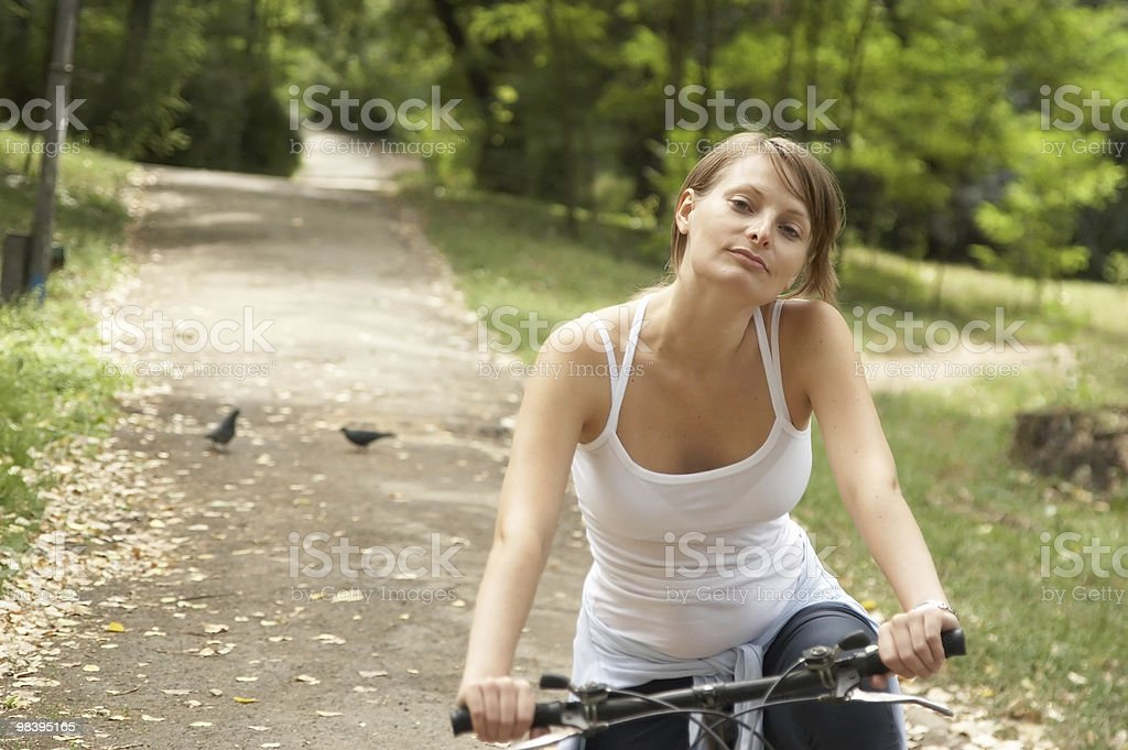 Woman cycling in a park royalty-free stock photo