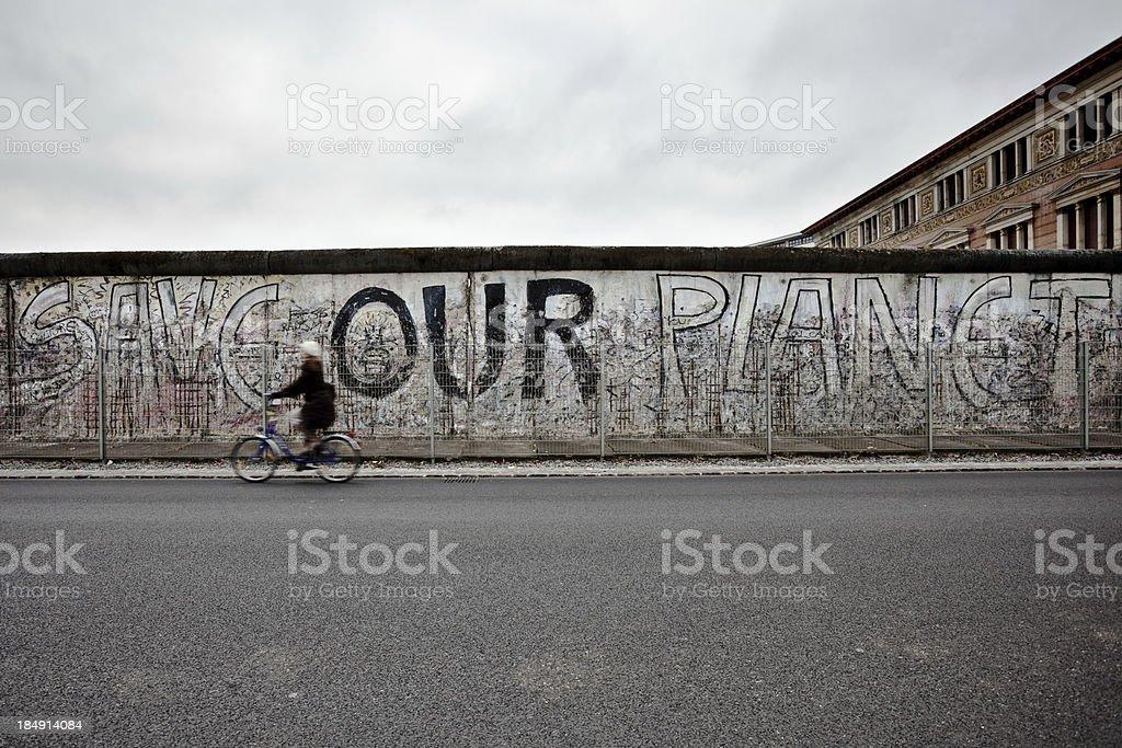 Frau Radfahren auf der Vorderseite der Berliner Mauer, East Side, Deutschland – Foto
