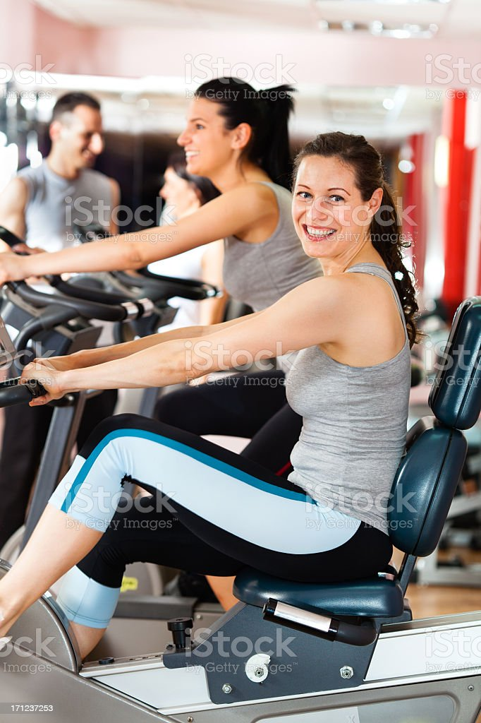 Woman cycling in gym stock photo