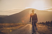 istock Woman cycling in sunset. 1134842667