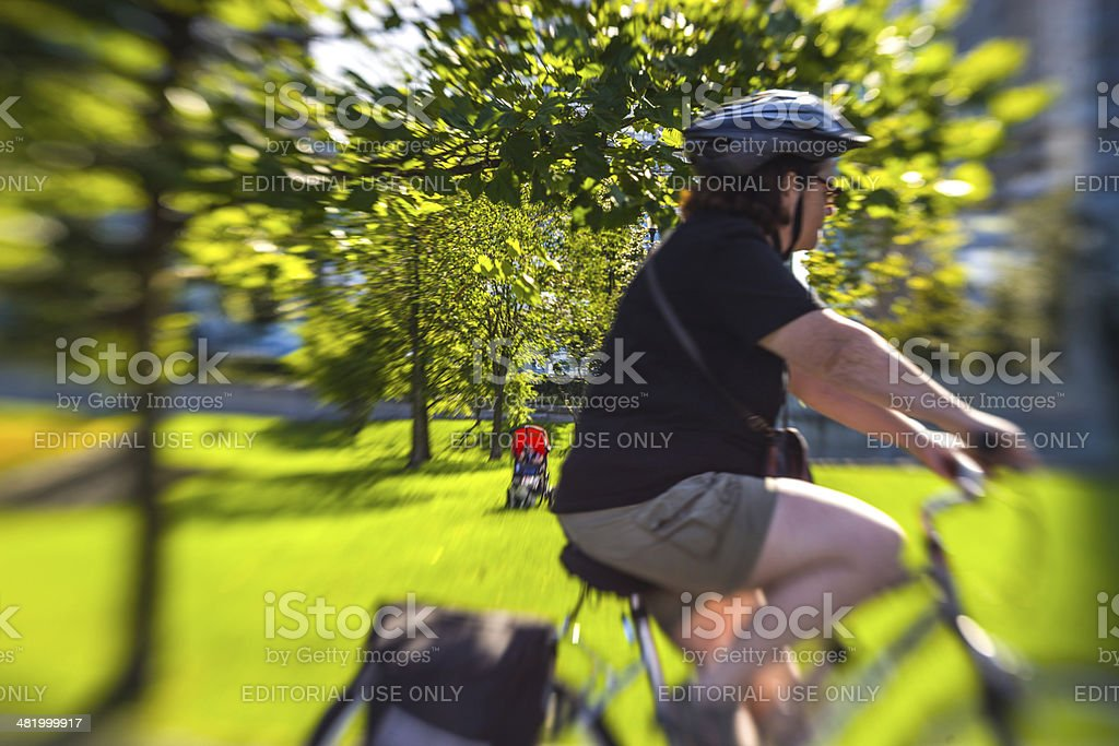 Woman cycling in Vancouver, lens baby shot stock photo