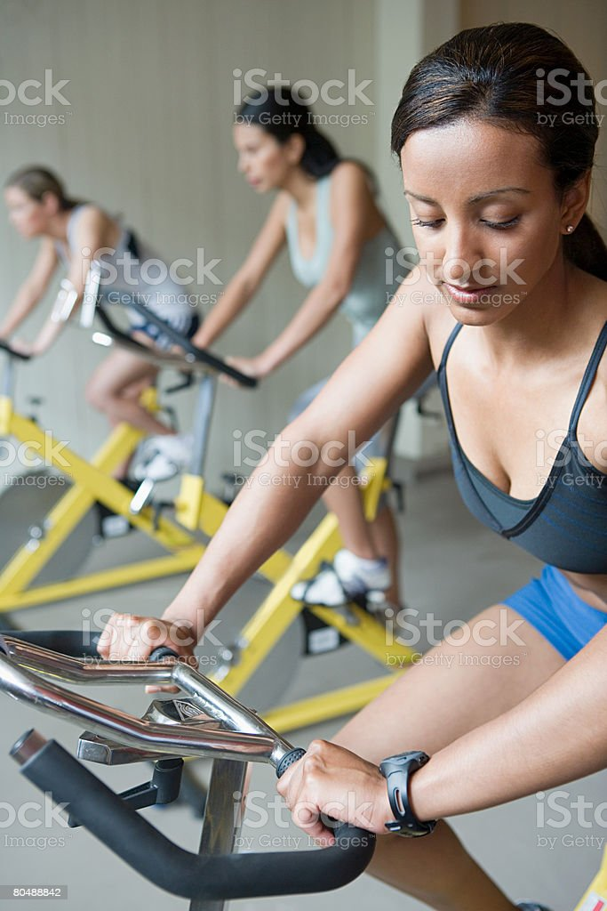 A woman cycling on an exercise bike royalty-free 스톡 사진