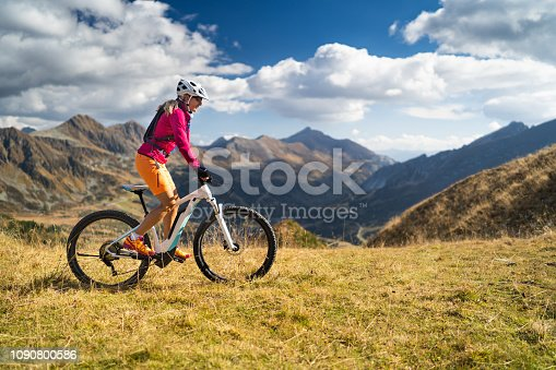 side view female biker happy woman cycling on her electric mountain bike high up in european alps on sunny day in autumn