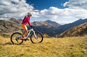 woman cycling on electric mountain bike high up in austrian mountains alps