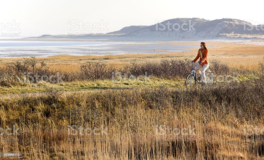 Woman cycling seaside on island Sylt stock photo