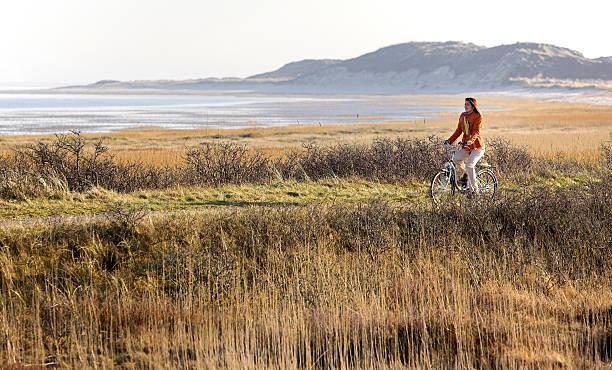 frau fahrradfahren am meer auf der insel sylt - sylt urlaub stock-fotos und bilder