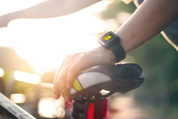 woman cyclist hand with smart watch on saddle bicycle at summer trail. stock photo