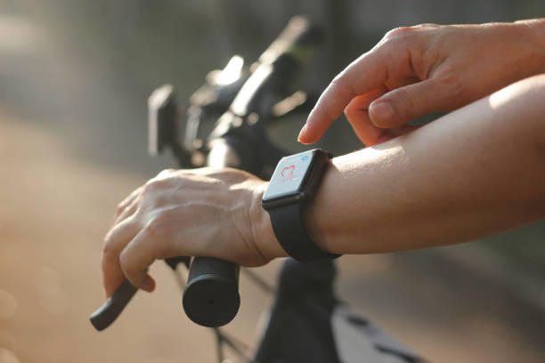 Woman cyclist hands with heart rate icon on smart watch, bicycle at summer trail. All on screen are design up. stock photo