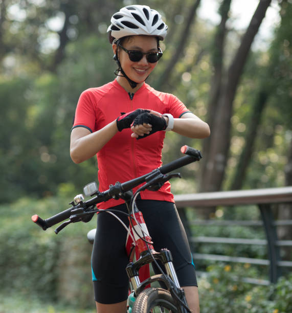 Woman cyclist looking at her smartwatch while riding bike on sunny day stock photo