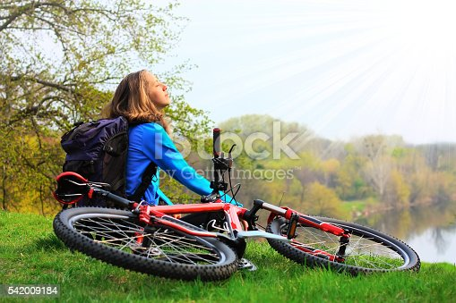 969439086istockphoto Woman cyclist relaxing, face to the sun's rays 542009184