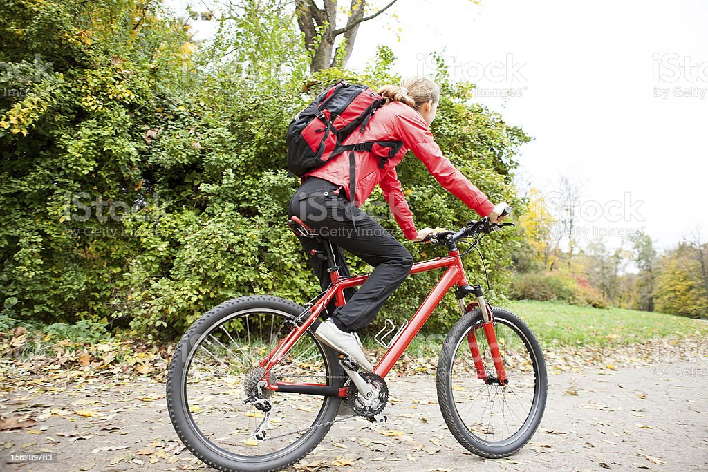 Woman cyclist riding a bike in autumn park royalty-free stock photo