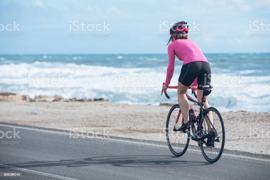 ciclista mujer monta en bicicleta en la carretera cerca del mar foto de stock libre de derechos