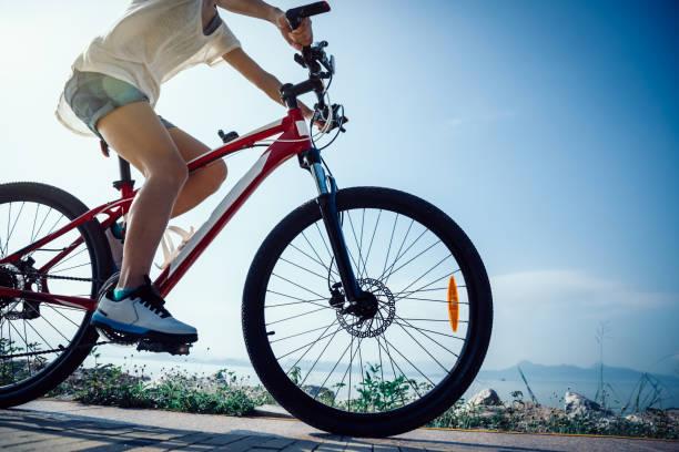 Radfahrerin fährt am Sonnenaufgang Mountainbike – Foto