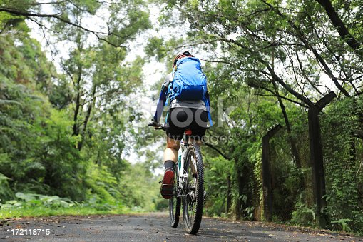 Woman cyclist riding mountain bike on tropical rainforest trail