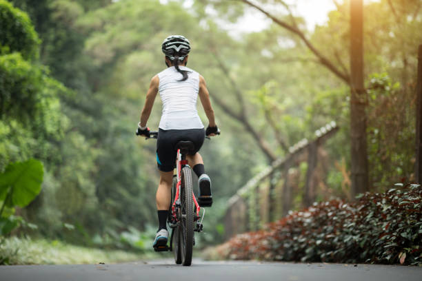 Woman cyclist riding mountain bike on tropical rainforest trail stock photo