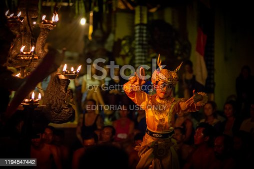 Ubud, Bali, Indonesia - September 3, 2017: Woman dancer in traditional costume at a kecak fire dance ceremony. Taken in the evening with no flash, mostly candle lighting resulting in some image noise.