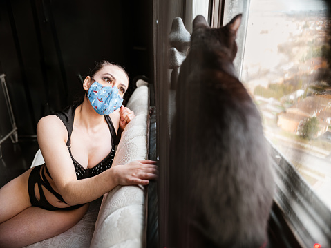 Sign of times with COVID-19: Night club female performer playing with the black cat during the practice break. Interior of Entertainment club during the day. She is wearing face mask.