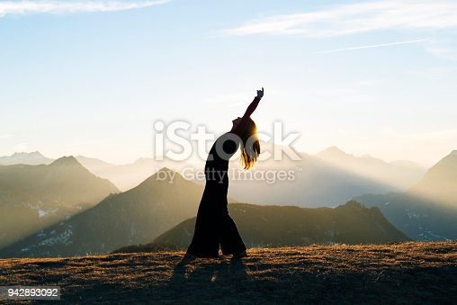 She is bending backwards as sun rises behind her.  She is in an open meadow, Ticino Canton