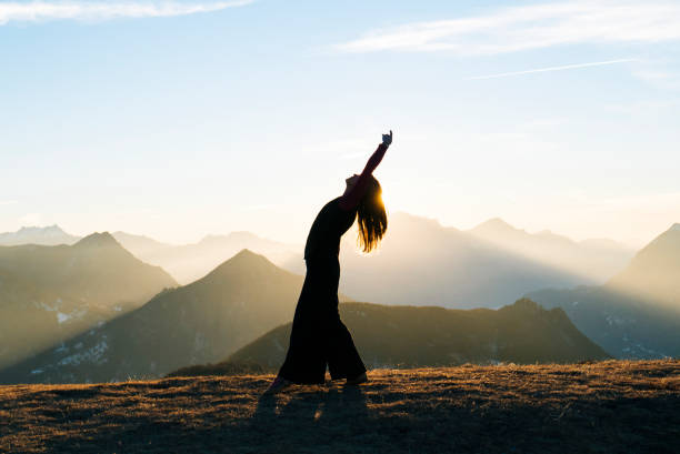 woman dances at sunrise in the mountains - mindfulness stock photos and pictures