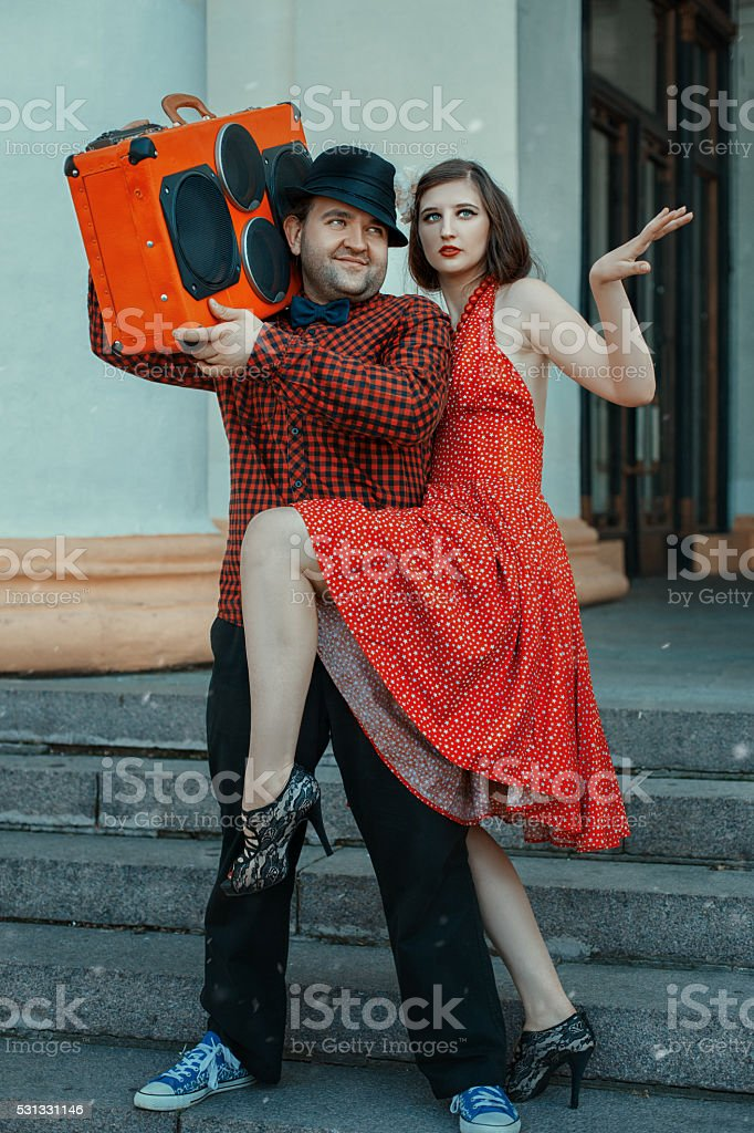 Woman dancing around the men. stock photo