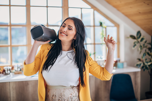 One beautiful young woman having fun at home, dancing while holding wireless speaker.