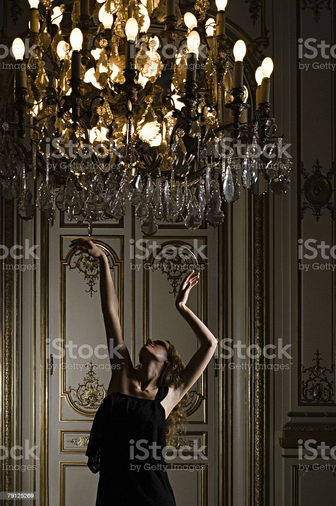 Woman dancing beneath chandelier 免版稅 stock photo