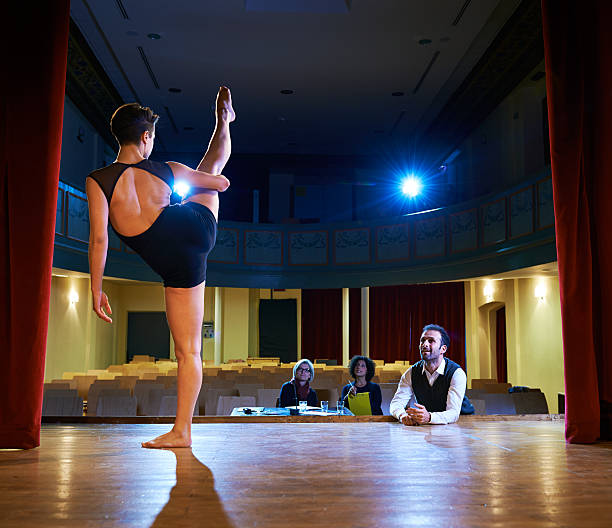 woman dancing for audition with jury in theater - audition stock photos and pictures