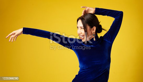 Woman dancing front of yellow background.