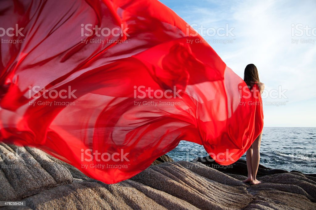 Woman dancing in red dress that flying on the wind stock photo