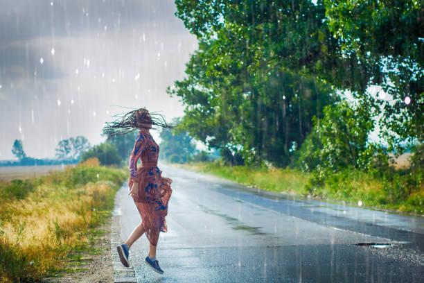 Woman dancing in the rain stock photo