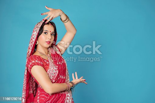 Studio portrait of young woman in traditional Indian sari dress wearing bracelets and nose ring when dancing
