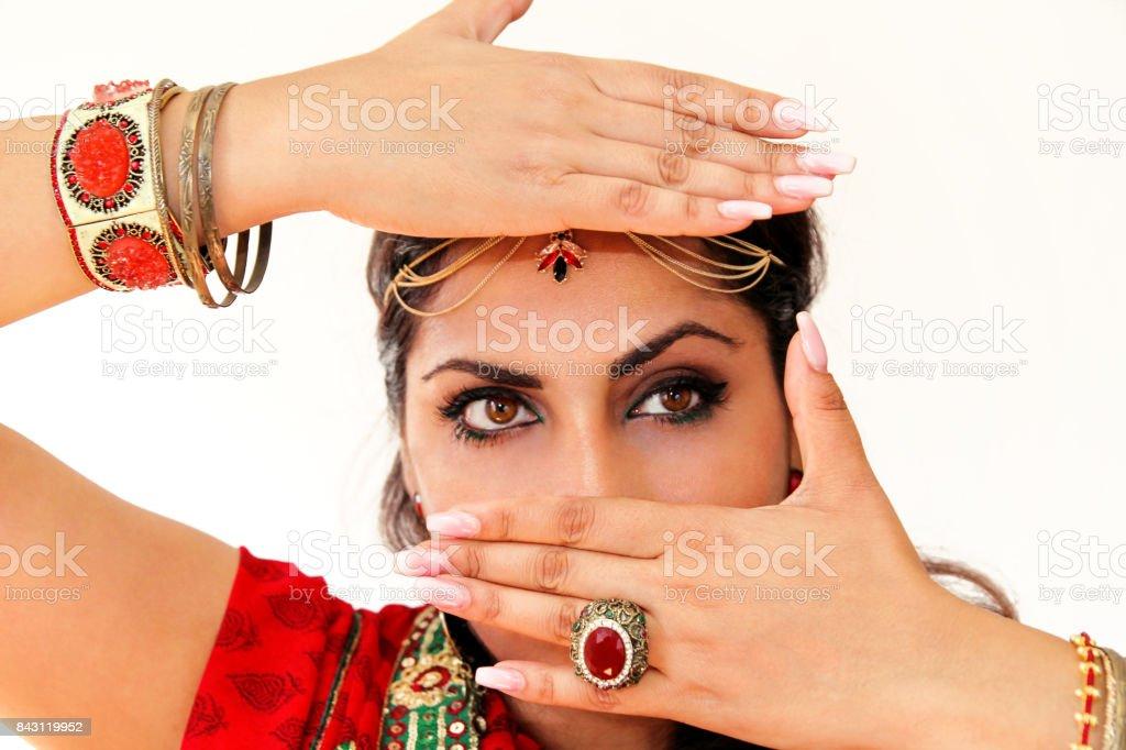 Mulher dançando a dança indiana no vestido nacional. Um retrato bonito menina bonita em vermelho Hindu Saree, chifre para o movimento de dança indiana. Dançarino indiano em roupas tradicionais. Dança de Bollywood. Beleza. - foto de acervo